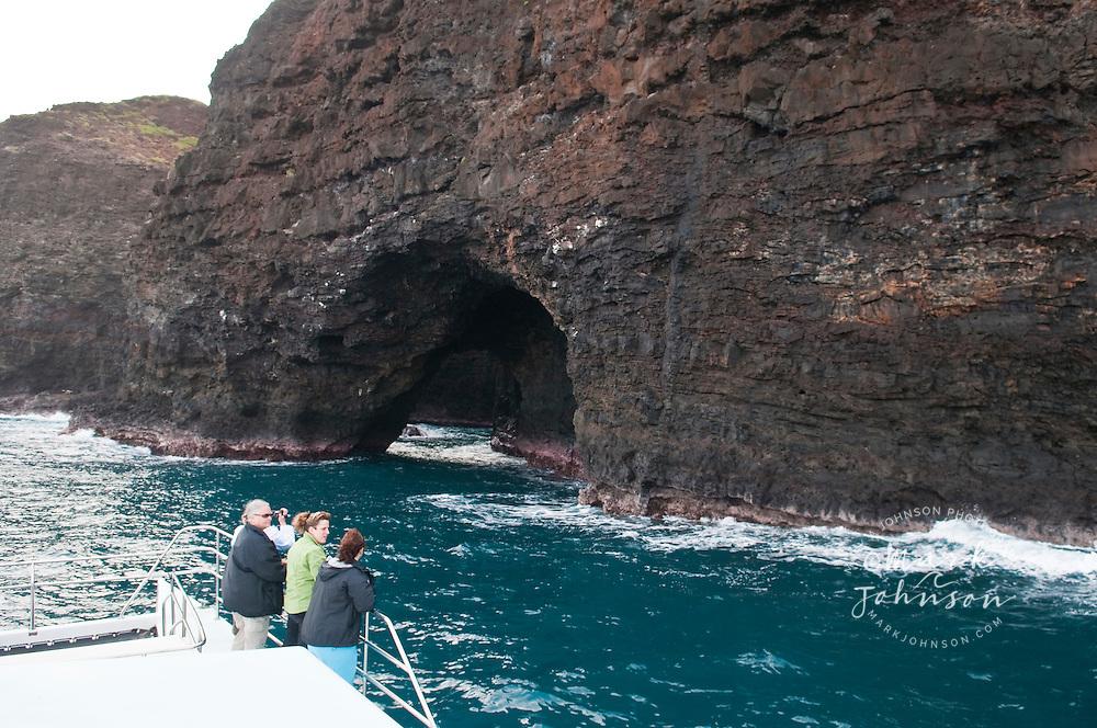 Tourists on sight-seeing boat off the Na Pali coast, Kauai, Hawaii