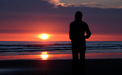 © Licensed to London News Pictures. <br /> 17/04/2015. <br /> <br /> Saltburn, United Kingdom<br /> <br /> A woman stands on the beach and watches a spectacular sunrise at Saltburn in Cleveland.<br /> <br /> Photo credit : Ian Forsyth/LNP