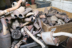 Pile of old catalytic converters at a metal recycling centre,