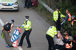 Ockham, UK. 21st September, 2021. A Surrey Police officer pulls an Insulate Britain climate activist from the anticlockwise carriageway of the M25 between Junctions 9 and 10. Activists briefly halted traffic on both carriageways of the motorway as part of a campaign intended to push the UK government to make significant legislative change to start lowering emissions.