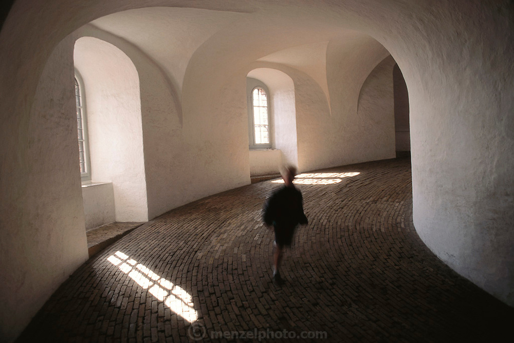 A young boy runs down the curving ramp of the Rundetarn/round tower. Copenhagen, Denmark.