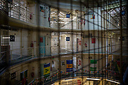 Landscape view across the central hall to the multiple levels of Wing C and E and of Her Majesty's Prison Pentonville, London, United Kingdom.  Pentonville is a local prison and holds Category B and C males and A Wing is for this who are on remand and convicted. The prison was built in 1816 as a modern prison and was uniquely designed for rehabilitation.  It was the first radial design prison which allowed staff to view all 5 wings from the central hall. The prison remains largely untouched from its original design.