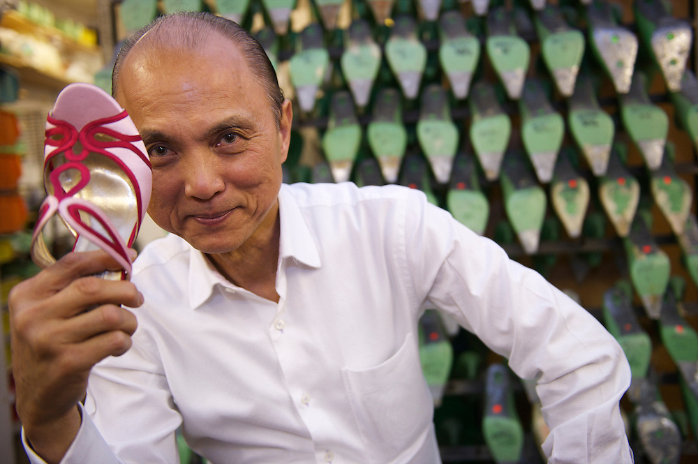 Holding a pair of bespoke shoes, fashion designer Jimmy Choo poses in his studio on Cannaught Street, London, March 22, 2010.