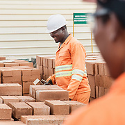 INDIVIDUAL(S) PHOTOGRAPHED: Mabande Mulewesi (left) and Laika James (right). LOCATION: 14Trees Manufacturing Site, Lilongwe, Malawi. CAPTION: Mabande smiles while moving freshly made Durabrics, as his colleague Laika James observes.