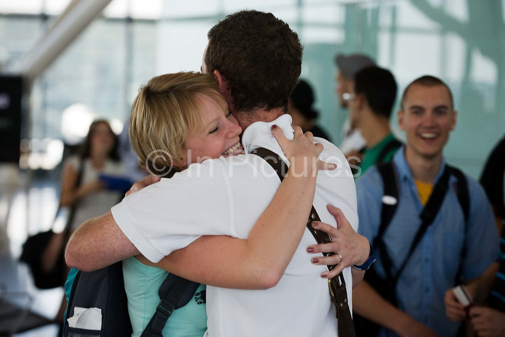 """Honeymooners cuddle in front of other passengers before their round-the-world adventure, leaving from Heathrow Airport's Terminal 5B. The couple are seen embracing at the departure gate as the remaining air travellers filter through the last security checks and board their long-haul flight. The young lady has a look of contentment on her face, the look of happiness and comfort in the arms of her new husband and they hug with all the affection of young love and trust. Another passenger grins in their direction during this show of devotion. From writer Alain de Botton's book project """"A Week at the Airport: A Heathrow Diary"""" (2009)."""
