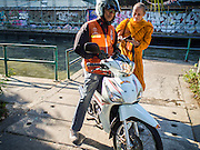 14 JANUARY 2015 - BANGKOK, THAILAND: A Buddhist monk pays his motorcycle taxi driver after getting a ride into the Ban Krua neighborhood of Bangkok. After months of relative calm following the May, 2014 coup tensions are increasing in Bangkok. The military backed junta has threatened to crack down on anyone who opposes the unelected government and relations with the United States have worsened after US diplomats called the continued prosecution of the formerly elected government deposed by the coup a political act rather than a criminal one. PHOTO BY JACK KURTZ