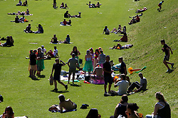© Licensed to London News Pictures. 15/07/2021. Edinburgh, Scotland, UK.  People enjoy a hot afternoon in Princes Street Gardens in Edinburgh as warm weather continues in Scotland. According to the Met Office, a high of 23 degrees celsius is forecast for the rest of the week. Scotland's first minister, Nicola Sturgeon has said that Scotland will move to a 'modified' form of level 0 on 19 July and 15 adults from 15 households can meet outdoors in a private garden or public place. Photo credit: Dinendra Haria/LNP