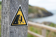 Warning sign for walkers along the coastal path warns of dangerous cliffs on 17th August 2021 in Newport, Pembrokeshire, Wales, United Kingdom. Newport is a town, parish, community, electoral ward and ancient port of Parrog, on the Pembrokeshire coast in West Wales at the mouth of the River Nevern in the Pembrokeshire Coast National Park.