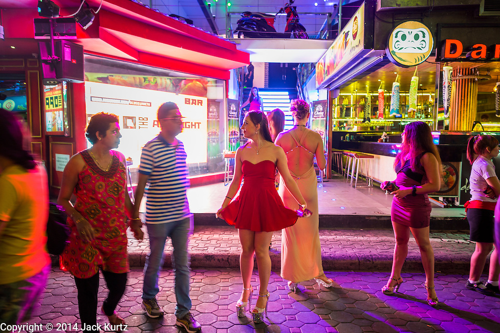 """26 SEPTEMBER 2014 - PATTAYA, CHONBURI, THAILAND: People in front of a go-go bar that advertises dancers from Russia on Walking Street in Pataya. Pataya, a beach resort about two hours from Bangkok, has wrestled with a reputation of having a high crime rate and being a haven for sex tourism. After the coup in May, the military government cracked down on other Thai beach resorts, notably Phuket and Hua Hin, putting military officers in charge of law enforcement and cleaning up unlicensed businesses that encroached on beaches. Pattaya city officials have launched their own crackdown and clean up in order to prevent a military crackdown. City officials have vowed to remake Pattaya as a """"family friendly"""" destination. City police and tourist police now patrol """"Walking Street,"""" Pattaya's notorious red light district, and officials are cracking down on unlicensed businesses on the beach.     PHOTO BY JACK KURTZ"""