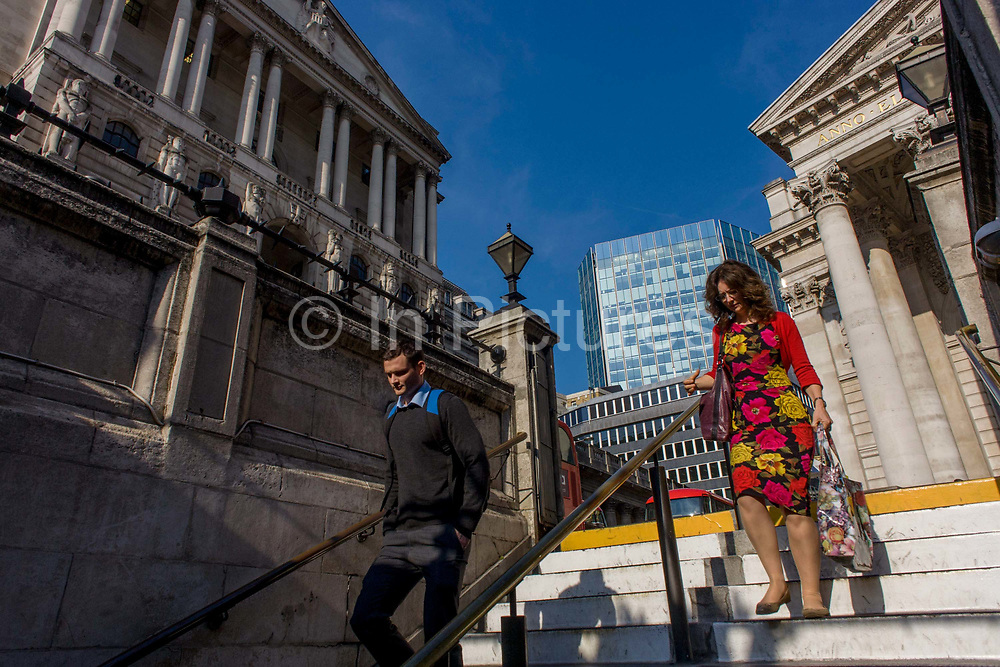 Bank of England on the left and neo-classical architecture of Cornhill Exchange, City of London. The man and lady are about to descend underground to Bank tube (subway) station beneath the converging columns of the famous Bank of England and Cornhill Exchange at Bank Triangle in the City Of London, the financial district, otherwise known as the Square Mile. They are homeward bound in the afternoon, their commuting exodus to be shared by a daily working population of 311,000. This perspective suggests a bank and its architecture looking powerful and influential in the UK's economy. The pillars give a sense of establishment, a scene of classic stability and strength.