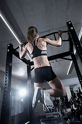 Rear view of a mid adult woman doing pull-ups in the gym, Bavaria, Germany