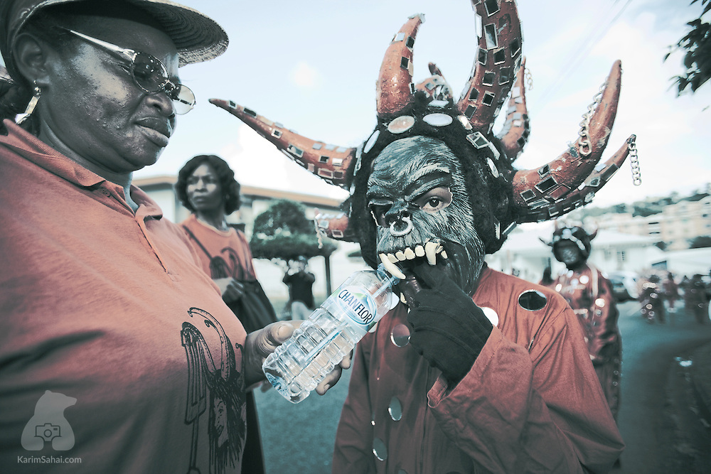 A boy wearing a devil's mask sips water from a bottle during the popular carnival in Le Lorain, Martinique; 19 February, 2006. In Martinique and throughout the Caribbean, Carnival festivities are an important part of the culture. A large segment of the population participates in large street parades wearing elaborate costumes.