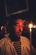 The Baptiste family. Devout Gypsy pilgrims with candles in the church at Saintes Maries de la Mer.<br /><br />Europe, France, Camargue, Saintes Maries de la Mer. Gypsies praying inside the church and crypt, to their patron Saint Sara and to the Saintes Maries. Marie Jacobe and Marie Salome. Catholic gypsies come from all over Europe to celebrate this festival in mid-May every year. There are many masses, christenings and private prayers during the gypsy pilgrimmage.