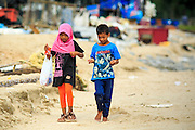 04 NOVEMBER 2012 - KAO SENG, SONGKHLA, THAILAND:  Children from Kao Seng walk along the beach in the town. Kao Seng is a traditional Muslim fishing village on the Gulf of Siam near the town of Songkhla, in the province of Songkhla. In general, their boats go about 4AM and come back in about 9AM. Sometimes the small boats are kept in port because of heavy seas or bad storms.    PHOTO BY JACK KURTZ