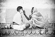 Varanasi, A man has a shave on the ghats at the anges River. Rendered in a sepia and purple split-tone.