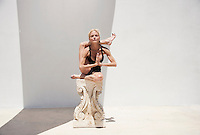Beautiful Mature Yoga Woman using a Greek Ionic Column as a prop for Eka Pada Sirsasana Pose, or leg behind the head posture. She is photographed in a white background studio with a graphic shadow. <br /> <br /> The Hard Light Studio is an innnovative open air studio with a white background that can be creatively controlled to to produce powerful figurative work. Built specifically to study athletic form, The Hardlight Studio can be adapted for portraiture and still life photography. Open all year in Joshua Tree, California. Use the contact to request more information and book a shoot.