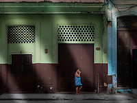 Woman, in a blue dress, stands out front of building in Havana.