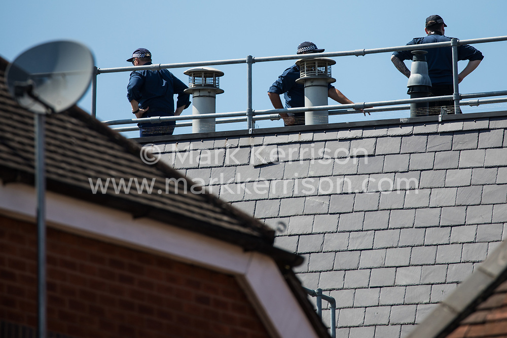 Windsor, UK. 13th June, 2021. Police officers watch over a street in the town centre from a rooftop shortly before the visit of President Biden to Windsor Castle. President Biden and First Lady Jill Biden were welcomed at Windsor Castle by the Queen following the G7 summit with a Guard of Honour followed by afternoon tea.
