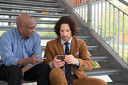 Two men African Caucasian sitting steps phone