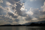 Sun shines through clouds above  the mangrove swamps, Cubatão