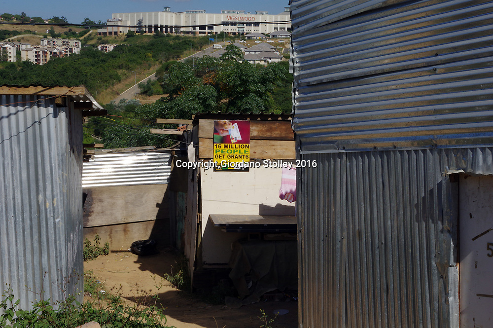 DURBAN - 3 May 2016 - Shacks in Clare estate in Durban, with a view towards the luxury Westwood Mall in Durban. A sign from the ruling African National Congress party proudly proclaims that 16 million people in the country receive social benefit grants. INformal settlements like Clare Estate are where battle line are drawn where the main opposition party, the Democratic Alliance hopes to make inroads against the ANC in the upcoming local government elections. Picture: Giordano Stolley/African Picture Press/APP