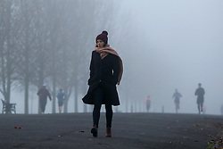 © Licensed to London News Pictures. 27/11/2020. London, UK. A woman walking in dense fog in Finsbury Park, north London. Freezing cold and foggy weather is forecast across many parts of the UK. Photo credit: Dinendra Haria/LNP