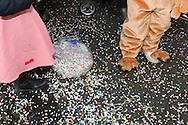 Carnaval in Aalst. confetti op de grond met verklede kindervoetjes.