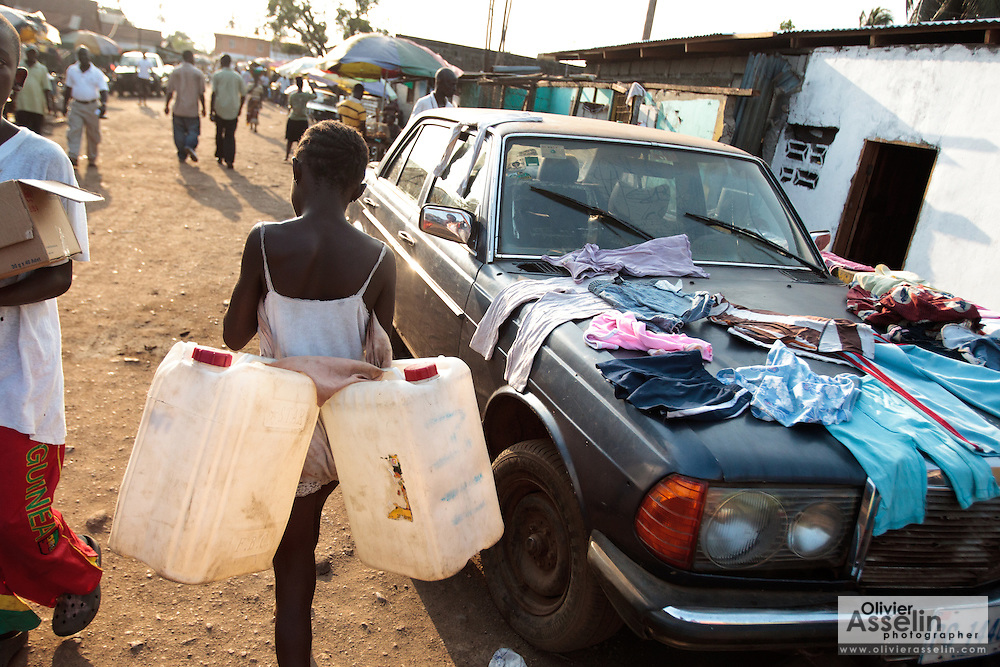 A girl carries two empty plastic jerricans as she heads to buy water in the Clara town slum in Monrovia, Montserrado county, Liberia on Thursday April 5, 2012.