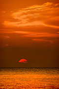A cloud bank on the western horizon hides half of the sun while the remainder glows red, lighting the Gulf of Mexico below and the clouds above.