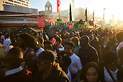 Carnival crowds gather in Ridley Road at the end of the carnival in the dying sun in East London, United Kingdom,Sept 11 2016. The annual Hackney Carnival took place on a hot summers day and the procession of dancers dressed in various outfits moved through the streets to much joy of the many bystanders.