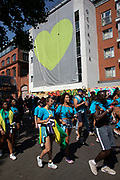 Green heart for Grenfell at Notting Hill Carnival on 26th August 2019 in West London, United Kingdom. A celebration of West Indian / Caribbean culture and Europes largest street party, festival and parade. Revellers come in their hundreds of thousands to have fun, dance, drink and let go in the brilliant atmosphere. It is led by members of the West Indian / Caribbean community, particularly the Trinidadian and Tobagonian British population, many of whom have lived in the area since the 1950s. The carnival has attracted up to 2 million people in the past and centres around a parade of floats, dancers and sound systems.