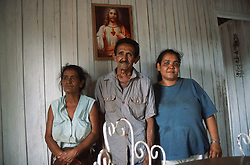 Family group with woman standing with her father and mother in farmhouse near Vinales; Pinar Province; Cuba,