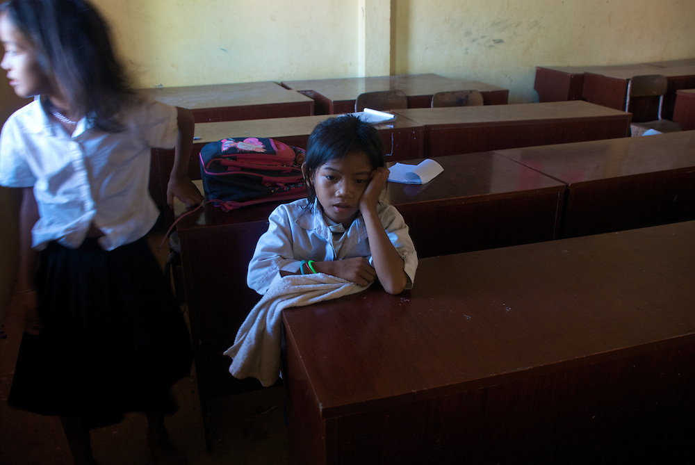 A young student sits in a classroom in the village at the base of Phnom Krom just outside of Siem Reap, Cambodia during recess.