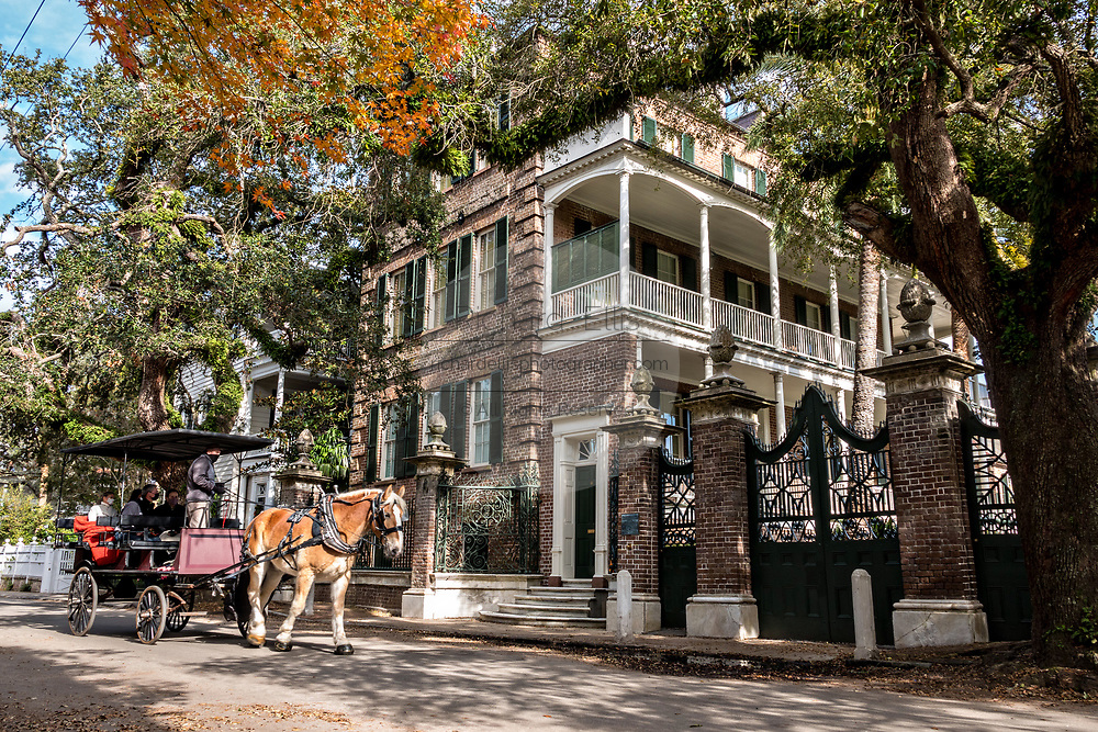 A horse drawn carriage tour passes the Simmons-Edwards House historic home on Legare Street in Charleston, SC.