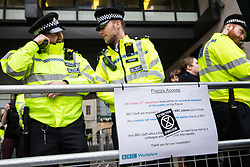 London, UK. 21st December, 2018. Police officers on duty outside Broadcasting House during a protest by environmental campaigners from Extinction Rebellion against the lack of coverage by the BBC of the climate change crisis.