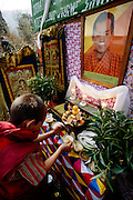 """(MODEL RELEASED IMAGE). As part of the celebration that marks the first electricity to come to this region of Bhutan, Chato Namgay (in red robe) lights the ritual butter lamps on an altar below the transformer on the power pole. Above a photo of the king, a sign reads: """"Release of Power Supply to Rural Households Under Wangdi Phodrang Dzon Khag to Commemorate Coronation Silver Jubilee Celebration of His Majesty, King Jigme Singye Wangchuk."""" (Supporting image from the project Hungry Planet: What the World Eats.) The Namgay family living in the remote mountain village of Shingkhey, Bhutan, is one of the thirty families featured, with a weeks' worth of food, in the book Hungry Planet: What the World Eats."""