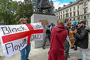 """A religiously motivated Christian man holds an English flag with words """"Black Babies Floyd Daily"""" in front of Winston Churchill statue during a Black Lives Matter rally in Parliament Square in London, Tuesday, June 9, 2020. Anger against systemic levels of institutional racism has raged through the city, and worldwide; sparked by the death of George Floyd, who was killed in Minneapolis, US, by a policeman who restrained him with force on 25 May 2020. (Photo/ Vudi Xhymshiti)"""