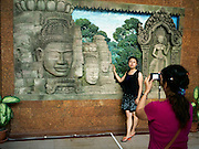 A Korean tourist takes a friend's photograph in front of a mural of Angkor at a gift and souvenir shop in Siem Reap.