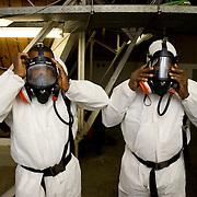 Nederland Rotterdam 3 december 2007.Asbestvewijderaars trekken werkkleding aan om beschermd te zijn tegen asbest dat zij gaan verwijderen uit de zolder van het Stadhuis Rotterdam .Asbestverwijderaars zijn vaak niet voldoende beschermd tegen kankerverwekkend asbest .Waarom dragen asbestverwijderaars van die maanpakken?.Een deskundig bedrijf dat asbest uit een gebouw verwijdert, zal zodanig maatregelen treffen dat zo min mogelijk asbestvezels in de omgeving terechtkomen, dat is ook de reden waarom Veenstra Milieutechniek een saneringsplan op stelt, nadat, er met een bouwkundige achtergrond, de constructie is vastgesteld.?Omdat op de werkplek zelf de risico's relatief het grootst zijn en de werknemers vrijwel dagelijks met asbest in aanmerking komen, dragen zij beschermende kleding, de zogeheten 'maanpakken'..Wat zijn precies de risico's van asbest?.De met het blote oog onzichtbare asbestvezeltjes kunnen, wanneer ze worden ingeademd, diep in de longen doordringen en op termijn bepaalde vormen van longkanker veroorzaken. ?In Nederland sterven naar schatting jaarlijks zo'n 600 mensen aan kanker die is veroorzaakt door (vaak beroepsmatige) blootstelling aan asbest. Meestal zitten er jaren tussen het inademen van asbestvezels en het moment van ziek worden. Het gevaar van asbest schuilt dus in het inademen van de vezels...Woon ik wel gezond?.?.Doe de test!.Ga verder.Asbest is een verzamelnaam voor een aantal in de natuur voorkomende mineralen, die zijn opgebouwd uit fijne, microscopisch kleine vezels. Losse asbestvezels zijn met het blote oog niet zichtbaar..Asbest is in het verleden veel gebruikt, bijvoorbeeld in gebouwen en woningen, vanwege de goede eigenschappen. Het is sterk, slijtvast en isolerend en bovendien goedkoop. Asbest is bestand tegen logen, zuren en hoge temperaturen. De grote risico's die asbest oplevert voor de gezondheid werden pas later bekend.?Asbestvezels kunnen bij inademing diep in de longen doordringen en op termijn buikvlieskanker, longvlieskanker