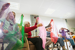 Girls and senior women doing gentle sports exercise with cloth in rest home