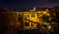 © Licensed to London News Pictures. 13/01/2021. Knaresborough UK. A early morning commuter train leaves a light trail as it crosses the viaduct in the picturesque town of Knaresborough in North Yorkshire at dawn this morning. Photo credit: Andrew McCaren/LNP