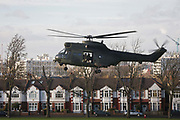 With homes beneath, a Royal Air Force Puma troop-carrying helicopter lands in Ruskin Park in the south London borough of Lambeth. It is believed that the RAF use various public spaces as part of emergency landing/evacuation location familiarisation in readiness of a future national emergency. The Puma (registration XW216 from 230 Squadron, RAF Benson) is used as battlefield helicopters within the Joint Helicopter Command and provide tactical troop and load movement by day or by night.