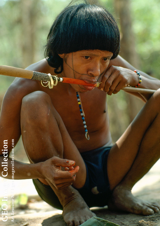 A Surui witch doctor, Perpera, uses his mouth to apply an organic dye to fiber wrapped around the shaft of an arrow.  For more information about the Surui Ind ians and the Seventh of September Funai Post, see No. 482.