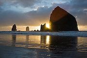 The pounding Pacific Ocean has eroded a bluff to create Haystack Rock, a 235-foot (72-meter) tall monolith (or sea stack), on Cannon Beach, on the Oregon coast. Haystack Rock is part of the Tolovana Beach State Recreation Site and is managed by Oregon Parks and Recreation below the mean high water (MHW) level, and above the MHW level by the Oregon Islands National Wildlife Refuge of the United States Fish and Wildlife Service.