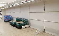 © Licensed to London News Pictures. 30/07/2021. London, UK. Nearly-empty shelves of bottled drink water in Sainsbury's, north London. Record breaking numbers of people have been forced to self-isolate after being alerted by the NHS Covid-19 app. The pingdemic has seen staff shortages at supermarkets, resulting in less stock making its way to supermarket shelves. Labour leader Sir Keir Starmer has demanded that the government brings forward the end to self-isolation from 16 August to 7 August. Photo credit: Dinendra Haria/LNP