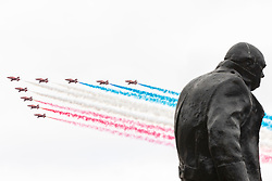 © Licensed to London News Pictures. 10/07/2018. London, UK. The RAF Red Arrows fly past the Winston Churchill statue in Parliament Square, trailing red white and blue smoke, to conclude toe RAF100 flypast which celebrates the centenary of the Royal Air Force. Photo credit: Rob Pinney/LNP