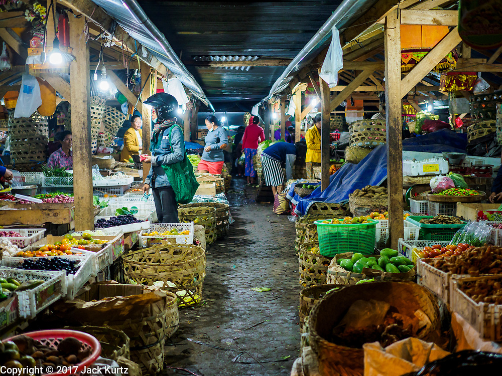 04 AUGUST 2017 - PAYANGAN, BALI, INDONESIA: Shoppers walk through the local market in Payangan, about 45 minutes from Ubud, before sunrise. Bali's local markets are open on an every three day rotating schedule because venders travel from town to town. Before modern refrigeration and convenience stores became common place on Bali, markets were thriving community gatherings. Fewer people shop at markets now as more and more consumers go to convenience stores and more families have refrigerators.      PHOTO BY JACK KURTZ