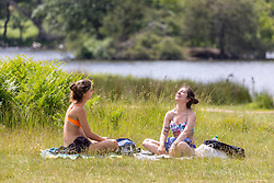 Licensed to London News Pictures. 16/06/2021. London, UK. Sunbathers enjoy the sunshine in Richmond Park, southwest London as weather forecasters predict a 30c scorcher today before storms hit the UK tonight. The Met Office have issued a four day yellow weather warning for thunderstorms and heavy rain for London and the South East with the possibility of lightening strikes and flooding of properties putting an abrupt end to the hot weather. Photo credit: Alex Lentati/LNP