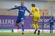 Oxford United defender Rob Dickie (4) battles for possession  with AFC Wimbledon striker Joe Pigott during the EFL Sky Bet League 1 match between Oxford United and AFC Wimbledon at the Kassam Stadium, Oxford, England on 13 April 2019.