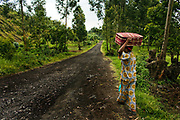 Esther, 23, at right, heads to the transit center as she carries her suitcase on her head in Buhimba, North Kivu. She walked like this for about half hour to the transit center. Ester said she was raped by two Rwandan rebels when she was farming in the field in June 2004. She was married and pregnant at that time, and lost her baby. Her husband left her after he visited Heal Africa three times. She return to her village in a volatile Rutshuru Territory 10 days later.